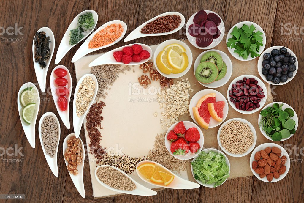 Display of assorted whole foods in white dishes on wood stock photo