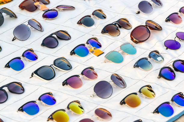 display of colorful sunglasses for sale in a street - sale lenses stock photos and pictures