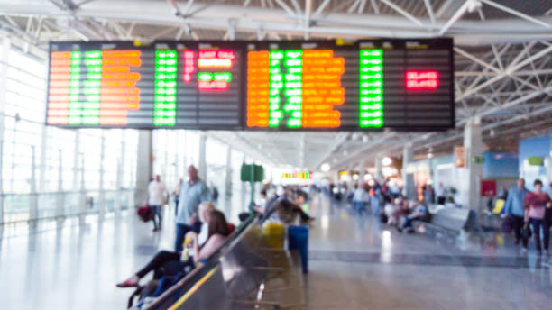 display of departure times with colorful lights at an airport - defocused people stock photo