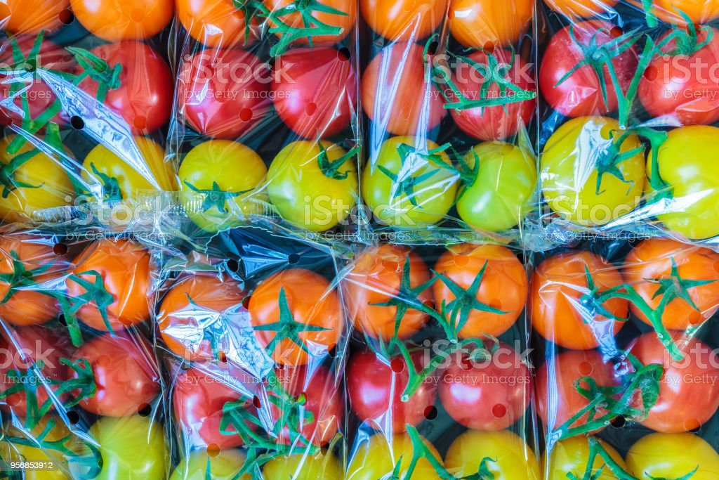 Display of fresh plastic wrapped cherry tomatoes stock photo