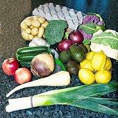 A mixed display of Australian fresh vegetables including Leek, Avocado, and Purple Cauliflower. Gosford City Farmers Markets. NSW, Australia.