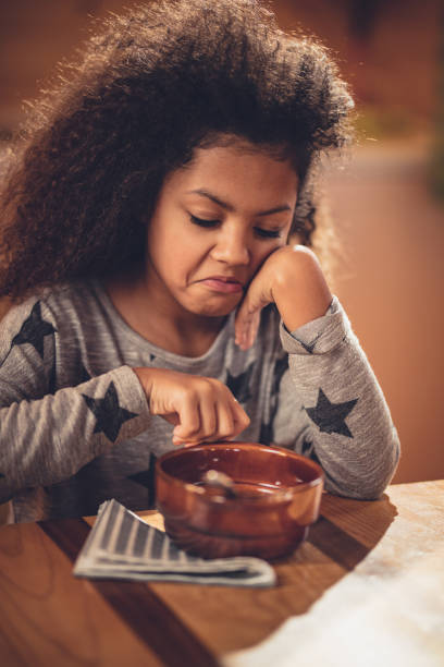 Displeased African American girl doesn't want to eat her breakfast. stock photo