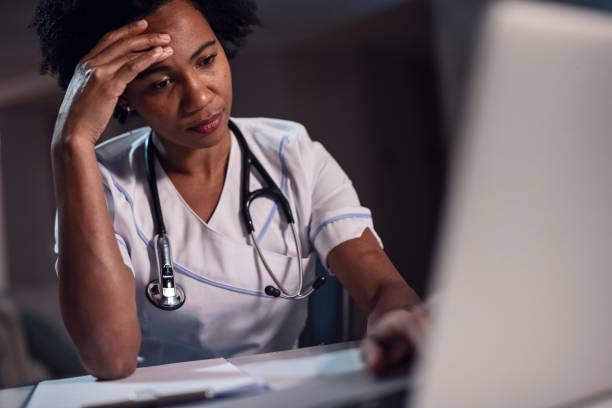 disgustado trabajador de la salud afroamericano usando el ordenador portátil en la oficina del médico. - trabajar hasta tarde fotografías e imágenes de stock