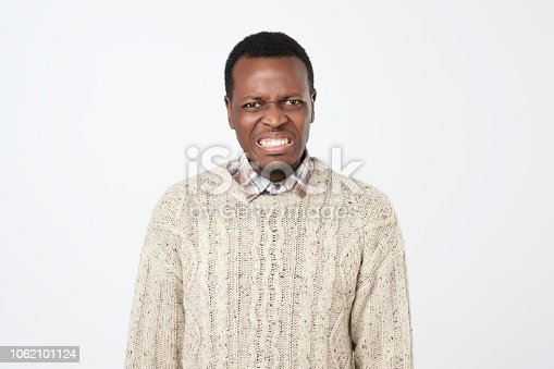 istock Displeased african man frowns face with displeasure, has irritated expression and clenches teeth 1062101124