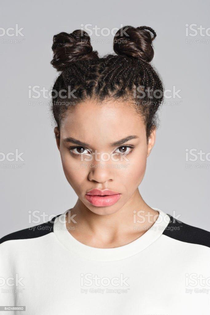 Displeased afro american teenager girl Studio portrait of angry afro american teenage woman looking at camera. Studio shot, grey background. 16-17 Years Stock Photo