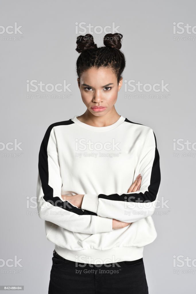 Displeased afro american teenager woman standing with arms crossed Studio portrait of angry afro american teenage woman standing with arms crossed and looking at camera. Studio shot, grey background. 16-17 Years Stock Photo