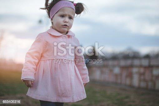 istock Displeased baby girl walking outside 653405316