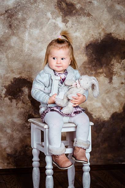 Verärgert Blondes Mädchen sitzt auf weißen Stuhl – Foto