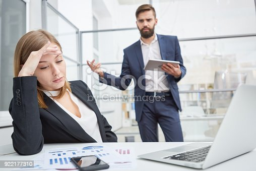 Angry displeased employer unsatisfied with employees work and berating young female manager leaning on hand and looking at report indifferently