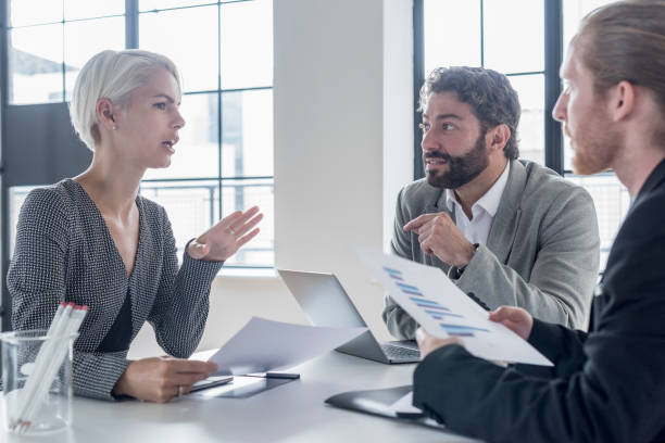 Displeased businesswoman gesturing toward two male colleagues in meeting stock photo