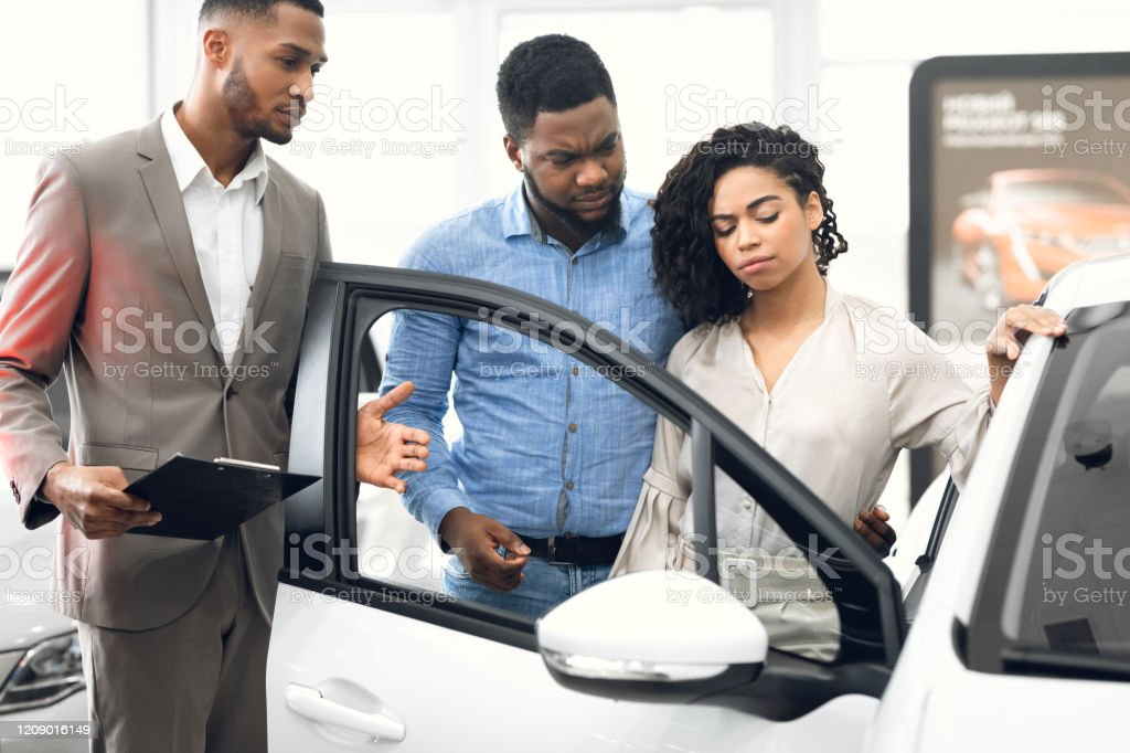 Displeased Car Buyers Choosing Automobile With Seller In Dealership Store Displeased Car Buyers Looking At Auto Choosing New Automobile With Seller Man In Dealership Store. Selective Focus Adult Stock Photo