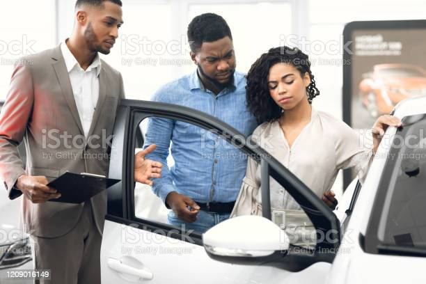 Displeased Car Buyers Choosing Automobile With Seller In Dealership Store Stock Photo - Download Image Now