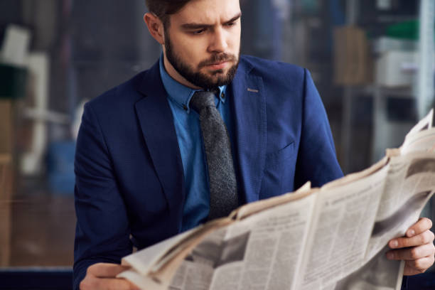 Displeased frowning male entrepreneur with beard concentrated on article reading newspaper in airport stock photo