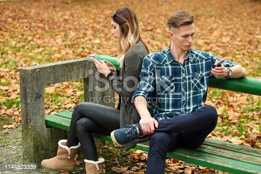 Couple sitting on a park bench. Man talking on phone and ignoring his angry grilfriend.