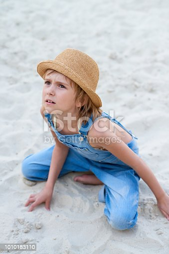 Pretty Caucasian little girl in denim overall and straw hat sitting on sandy beach and looking at someone with discontent