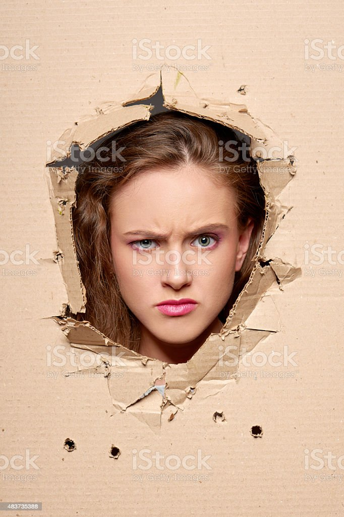 Displeased girl peeping through hole in paper stock photo