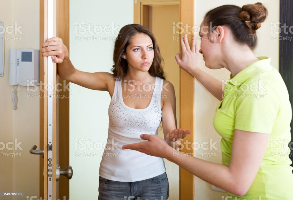 Displeased girl visiting neighbour stock photo