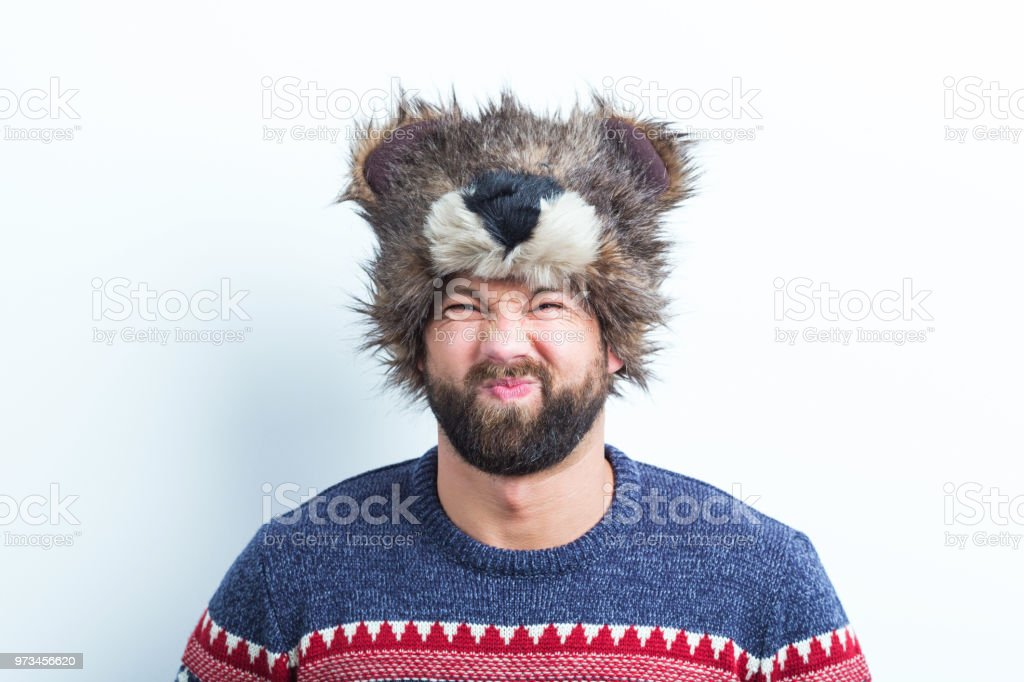 Displeased man in winter wear Portrait of displeased young man in sweater and funny winter cap on white background Adult Stock Photo