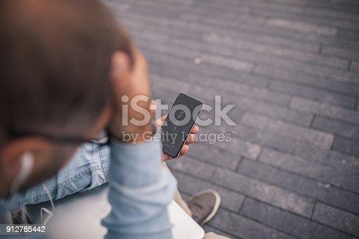Displeased man holding smartphone with broken screen
