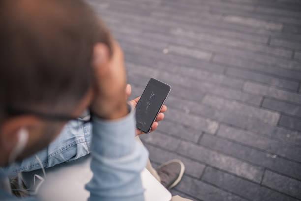 Displeased man with broken smartphone stock photo