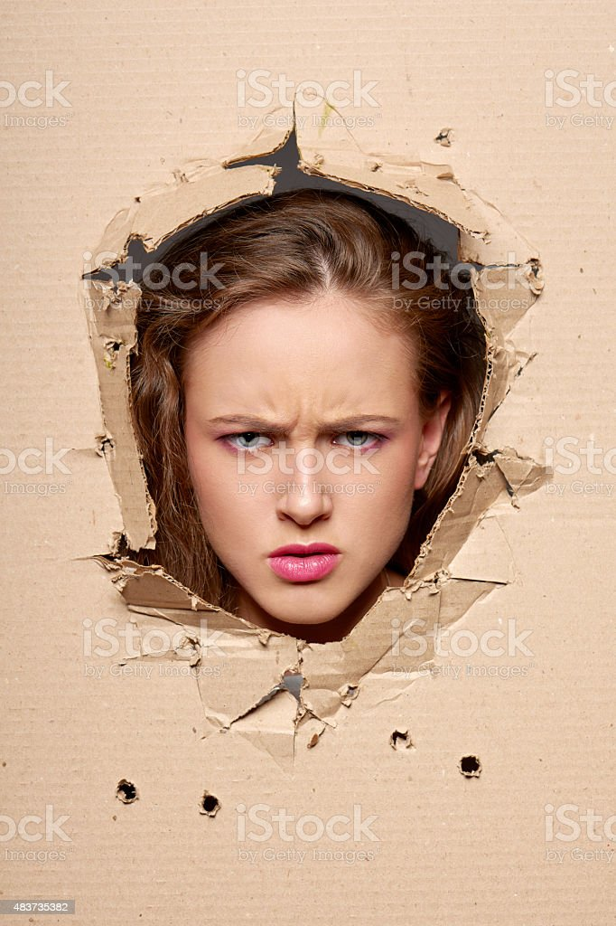 Displeased woman peeping through hole in paper stock photo