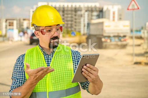 istock Displeased worker, engineer or architect  with digital tablet in front of truck 1177012919