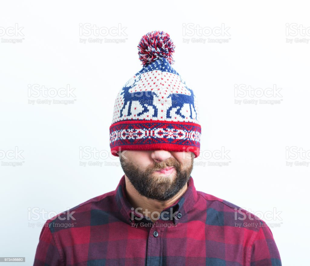Displeased young beard man in a winter cap Close up of displeased young beard man in a winter cap on white background Adult Stock Photo