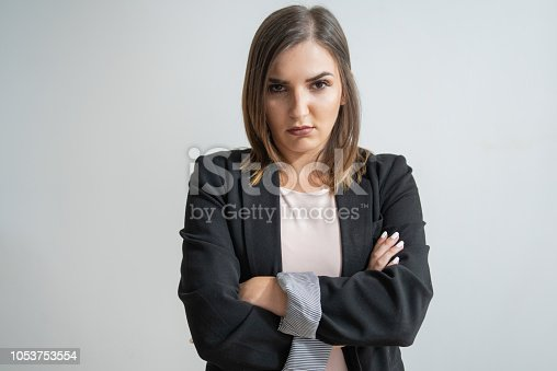 Displeased young Caucasian businesswoman with crossed arms. Pretty dark-haired manager in smart suit staring intently at camera with pressed lips. Dissatisfaction concept