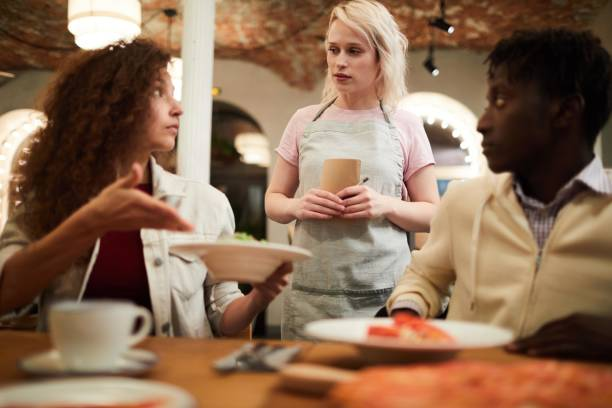 Displeased young female restaurant guest sitting at table and pointing at salad while talking to waitress and making negative assessment in modern loft cafe stock photo