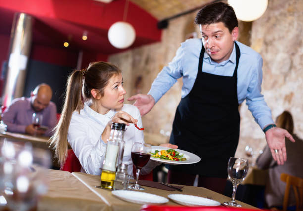 Displeased young woman conflicting with apologetic waiter because of poor quality of dish Displeased aggressive young woman conflicting with apologetic waiter because of poor quality of dish in restaurant waiter stock pictures, royalty-free photos & images