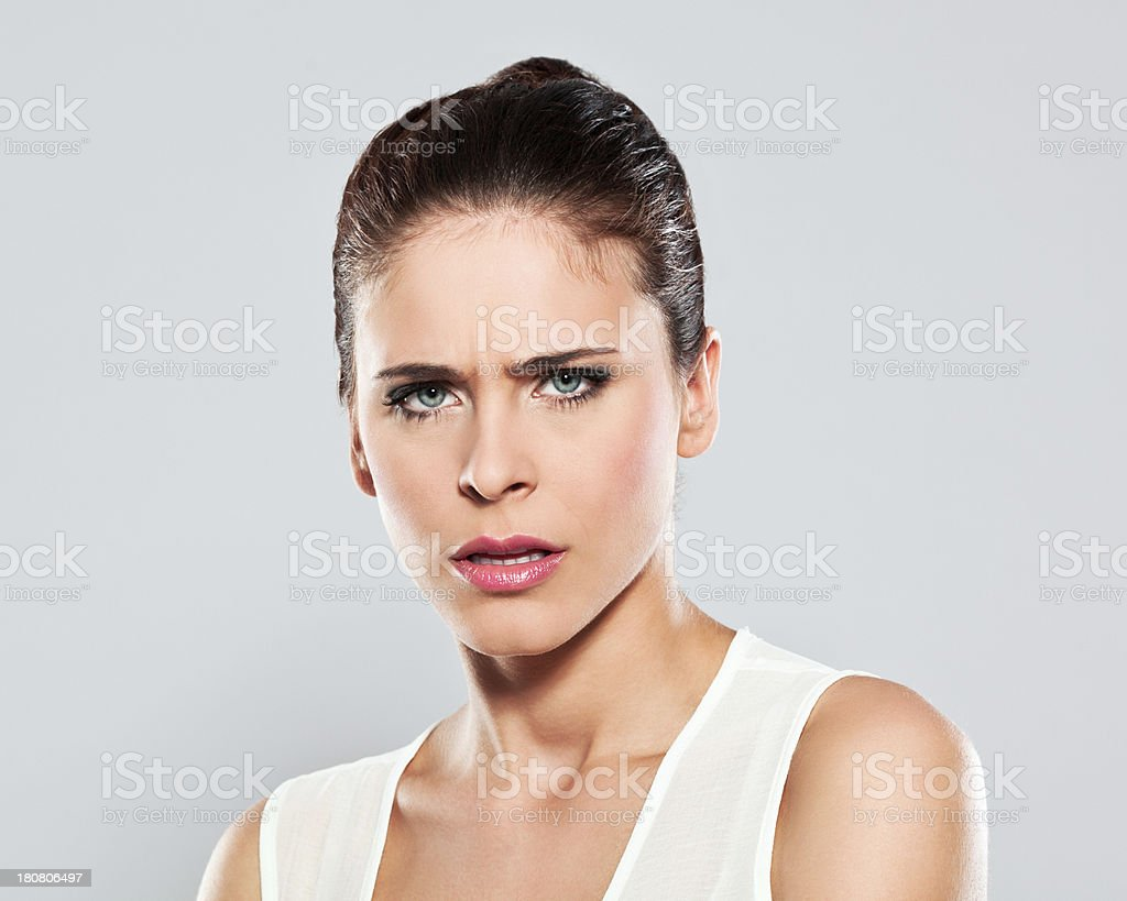 Displeased young woman, Studio Portrait Portrait of disappointed young woman staring at the camera. Studio shot on a grey background. 20-24 Years Stock Photo