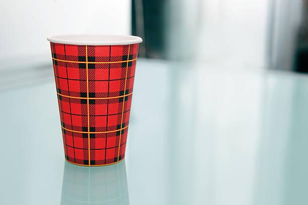 Einweg Kaffeebecher am gläsernen Esstisch. – Foto