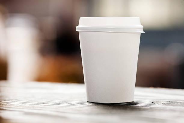 Wegwerfprodukt Kaffeetasse auf windowsill mit Blick auf die Stadt im Hintergrund. – Foto
