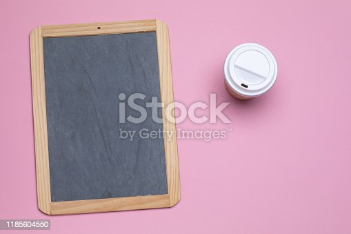 Paper cup of takeaway coffee and blackboard on pink background