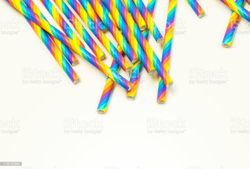Disposable colorful paper straws on white background