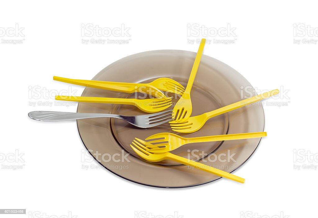 Disposable forks and one stainless steel fork on glass dish foto stock royalty-free
