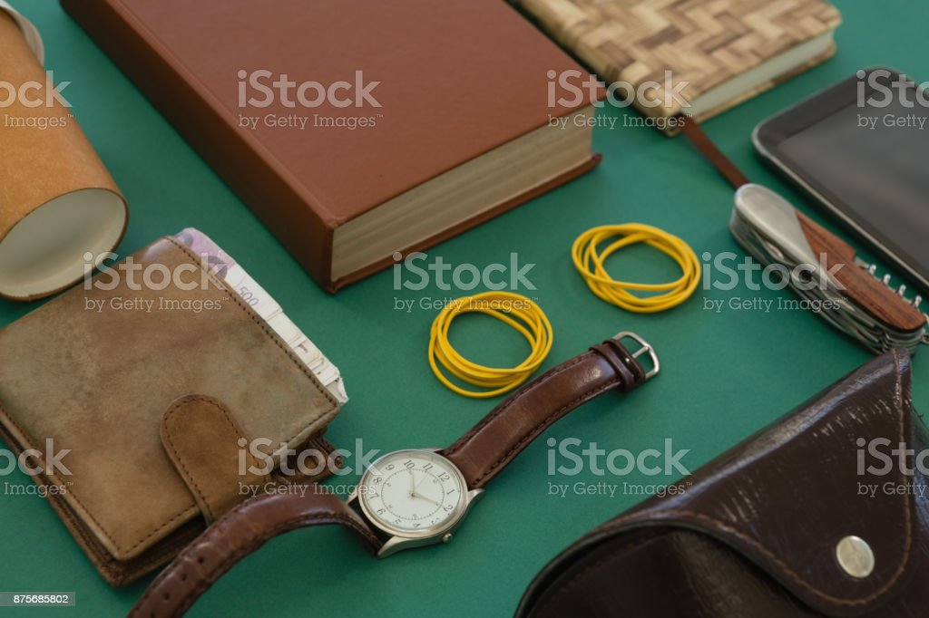 Disposable glass, wallet, organizer, wristwatch, pocketknife, mobile phone and sunglasses case on gr stock photo