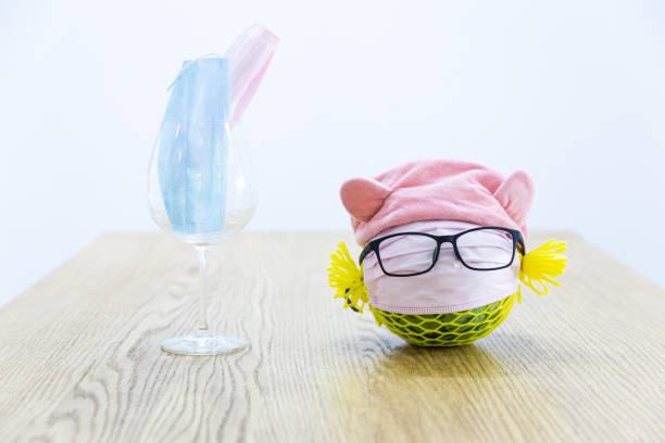 Una mascarilla médica desechable, copa de vino de frutas y vidrio en la mesa - foto de stock