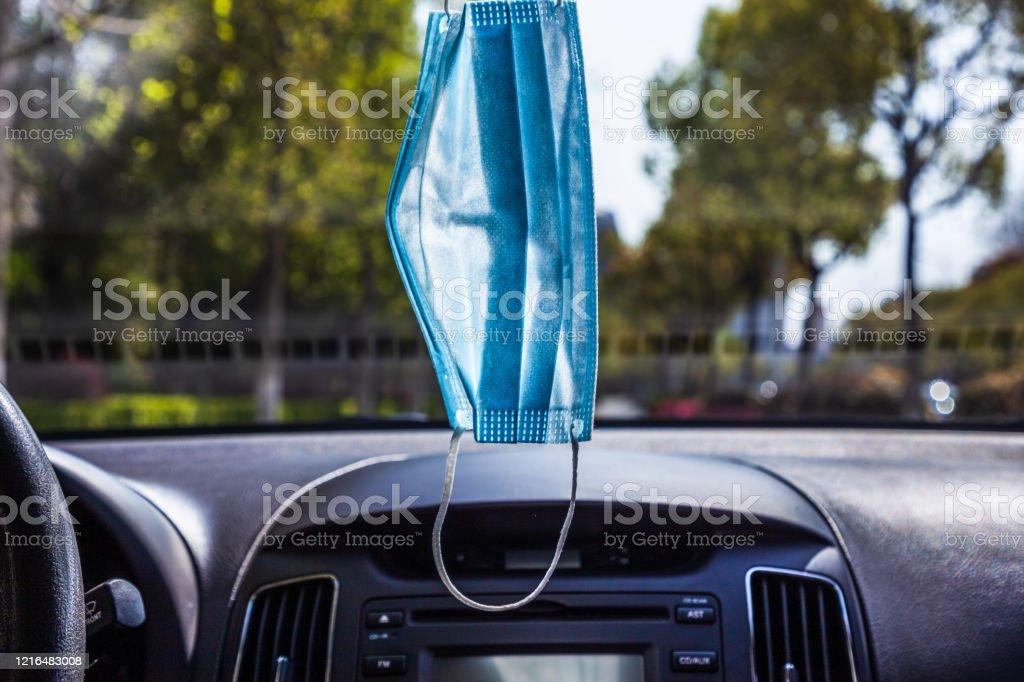 Una máscara médica desechable se cuelga en la parte delantera del coche - Foto de stock de Actuación - Conceptos libre de derechos