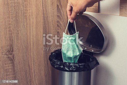 istock Disposable medical masks in a hand let down to infectious waste trash bin. 1216142588