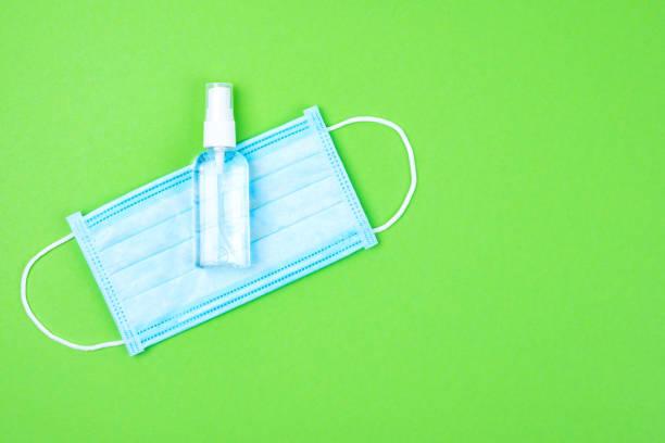 Einweg medizinische chirurgische Schutz gesichtsmaske mit antibakteriellen antiseptischen Spray für Hände Desinfektionsmittel auf grünem Hintergrund. Schutz vor Virus, Grippe oder Coronavirus Covid-19, 2019-nCoV. Ort für Text. – Foto