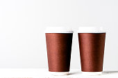 Disposable paper cup to coffee take away. Brown cups with lid for safety drinking.