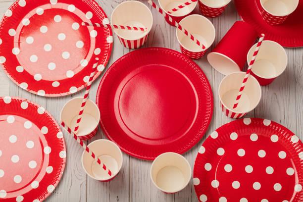 engångspappersprodukter köksredskap av röda och vita färg på en grå trä bakgrund. - glas porslin bildbanksfoton och bilder