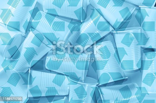 Several disposable plastic cups and recycling sing on a white background. Minimalistic ecologically clean still life. Green technology and ecology problem concept. Toned blue.