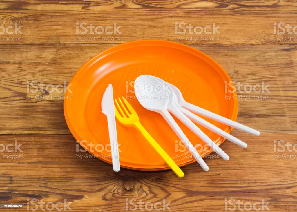 Disposable plastic plates, spoons, fork and knife on wooden surface photo libre de droits