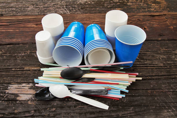 Disposable plastic straws, cups, cutlery stock photo