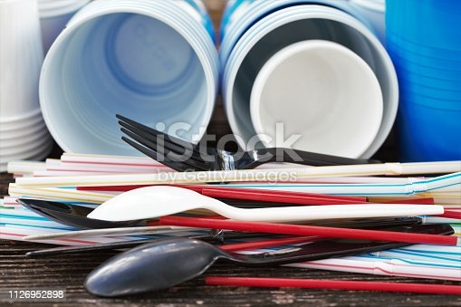 Plastic straws and twizzle stirring sticks, plastic cups in various sizes, plastic cutlery.  Single use plastic items, environmental issue, plastic pollution. Plastic dining or party supplies.