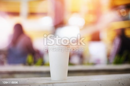 Disposable single take-out paper coffee cup in a shopping mall with unrecognizable people at the blurry background