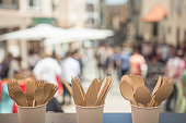 In the front of the photography is Disposable Wooden Cutlery – Eco Friendly Biodegradable Forks, Spoons, Knives. In the background is party on the street with plenty of people.