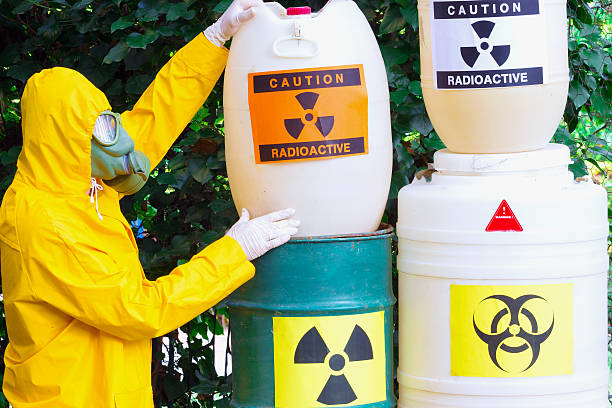 Disposal of radio active waste Chemist with the gas mask and the protective suit the disposal of radio active waste,photography toxic waste stock pictures, royalty-free photos & images